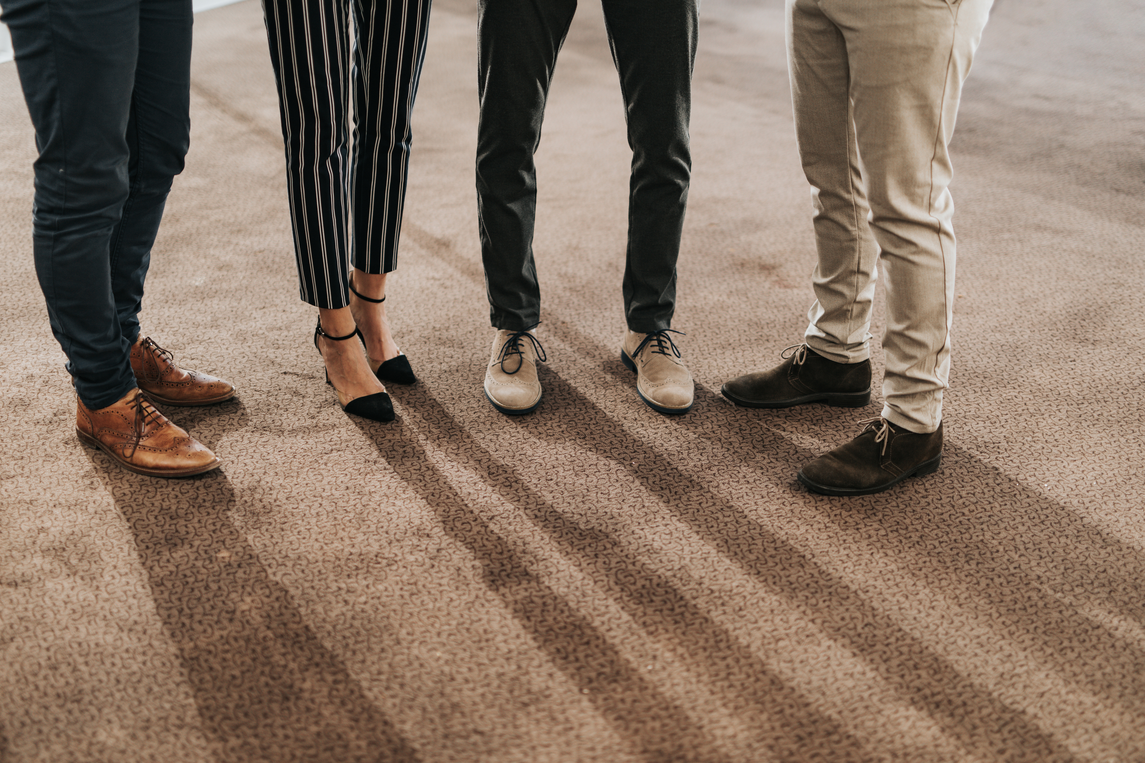 Group of unrecognizable business colleagues standing on carpet in the office. Copy space.